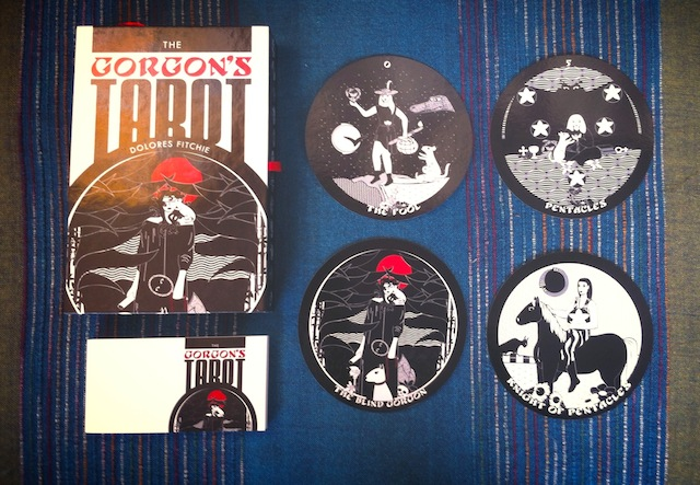The Gorgon's Tarot - a large box, small booklet and a selection of cards laid out - The Fool, Five of Pentacles, The Blind Gorgon and the Knight of Pentacles