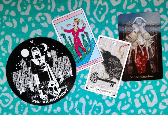 the hierophant tarot cards from four different decks, each showing a key somewhere within the image